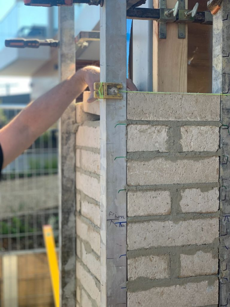 Image is of a bricklayer in Brisbane laying a front brick fence